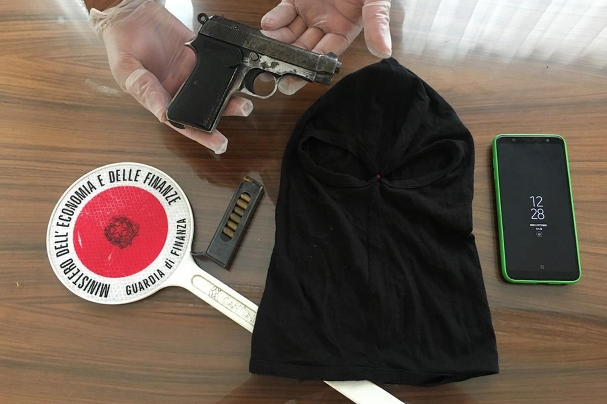 La pistola e il passamontagna sequestrati dalla Guardia di Finanza