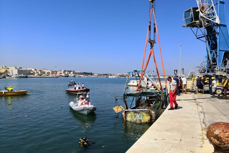 Le operazioni di recupero del peschereccio affondato nel porto di Molfetta