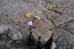 Accesso al mare tra carte e bottiglie di vetro